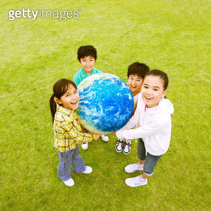 Group Of Small Children Standing On Grass Holding Earth Together - gettyimageskorea