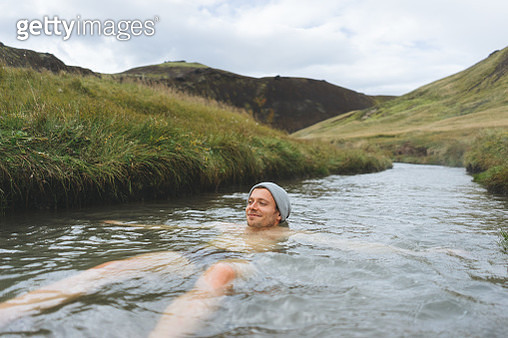 Man soaking in natural hot spring surrounded by nature in Iceland - gettyimageskorea