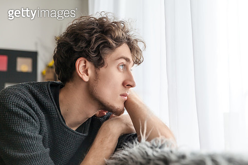 Portrait Of Young Man Looking Away At Home - gettyimageskorea