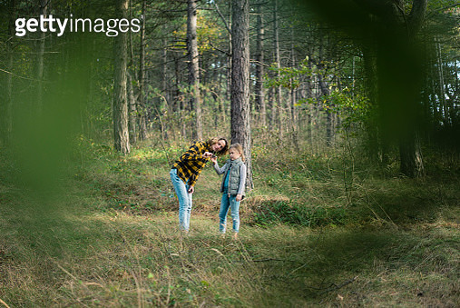 Mother and daughter exploring nature in the forest - gettyimageskorea