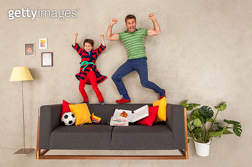 Father and son watching football in living room - gettyimageskorea