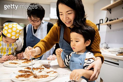 Mother finishing food and son eating snacks - gettyimageskorea