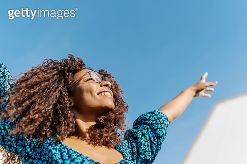 Young woman with African roots raising her arms - stock photo - gettyimageskorea