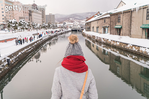 Rear View Of Woman Standing Against Canal In City During Winter - gettyimageskorea