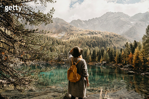 Switzerland, Engadin, woman on a hiking trip standing at lakeside in mountainscape - gettyimageskorea