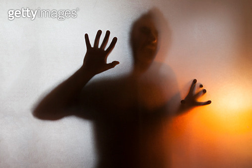 Man screaming with anger behind translucent surface - gettyimageskorea