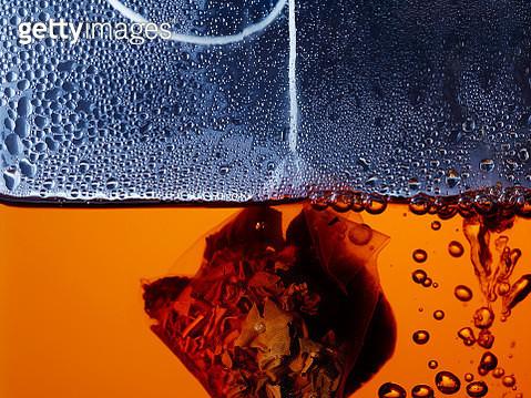 Tea bag inside orange liquid close up - gettyimageskorea