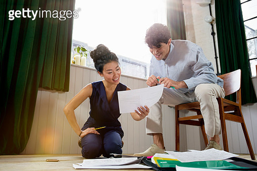 two people looking at paperwork in open plan office - gettyimageskorea