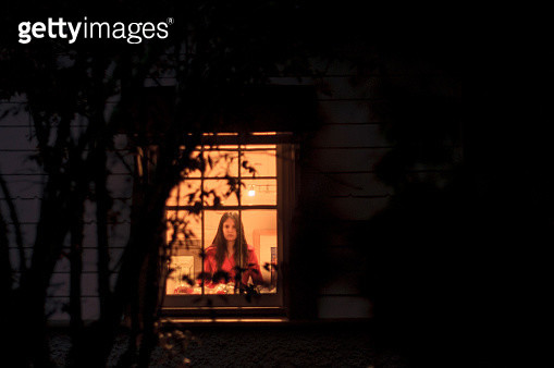 Young woman standing behind window, front view - gettyimageskorea