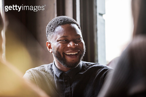 Man in a pub laughing with friends - gettyimageskorea