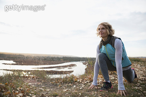 Woman practicing yoga low lunge on autumn hilltop overlooking lake - gettyimageskorea