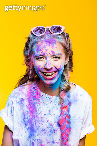 Portrait of excited teenage girl covered in colorful powder after holy festival, lauging at camera. Studio shot, yellow background. - gettyimageskorea