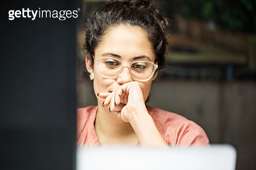 Thoughtful businesswoman using computer in office - gettyimageskorea