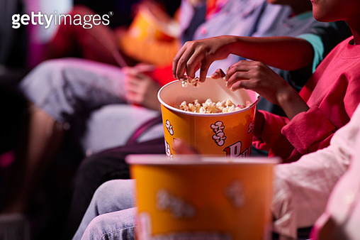 Midsection of friends sharing popcorn in theater - gettyimageskorea