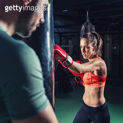Male Coach With Female Boxer Punching Bag In Gym - gettyimageskorea