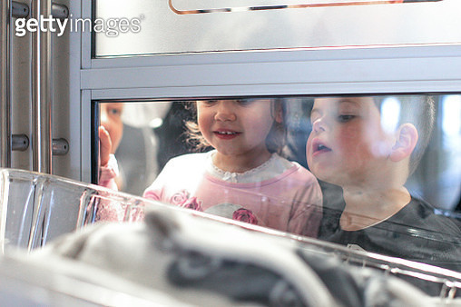 a Young boy and girl meet their new baby brother for the first time. - gettyimageskorea