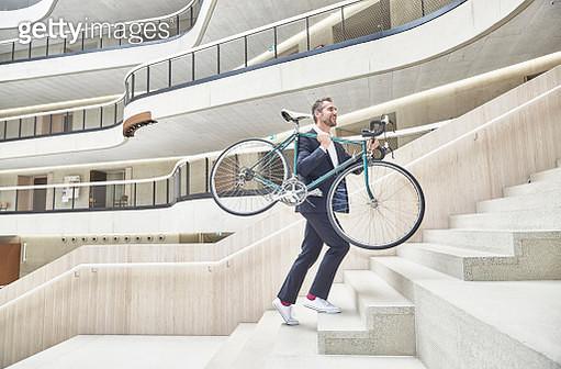Businesssman carrying bicycle in modern office building - gettyimageskorea