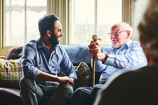 Young male doctor and senior man sitting on sofa and smiling during home visit - gettyimageskorea