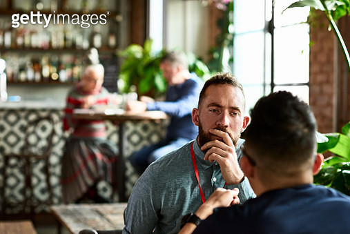 Man listening thoughtfully to business colleague in restaurant - gettyimageskorea