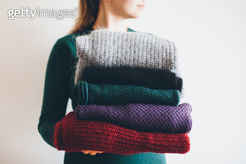 young woman in green sweater holds stack of five different knitted warm winter sweaters - gettyimageskorea