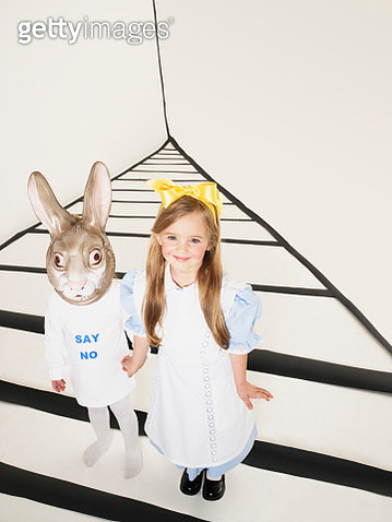 Portrait of smiling little girl dressed up as Alice in Wonderland hand in hand with girl with rabbit mask - gettyimageskorea