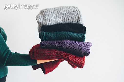 young woman in green sweater stand on the side holding stack of five different knitted warm winter sweaters - gettyimageskorea