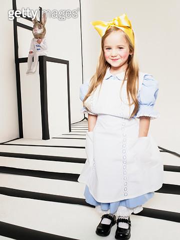 Portrait of smiling little girl dressed up as Alice in Wonderland - gettyimageskorea