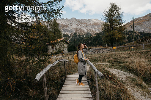 Switzerland, Engadin, woman on a hiking trip on a wooden bridge - gettyimageskorea