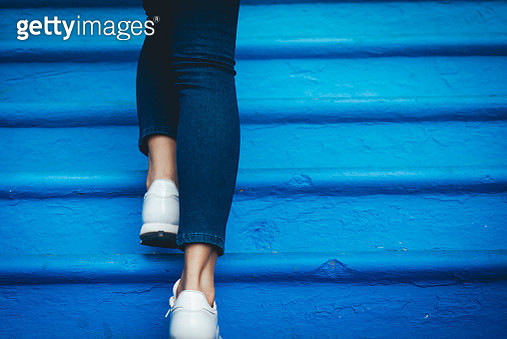 Low Section Of Woman Walking On Blue Steps - gettyimageskorea