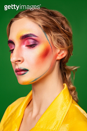 Calm woman in yellow coat and with makeup in studio - gettyimageskorea