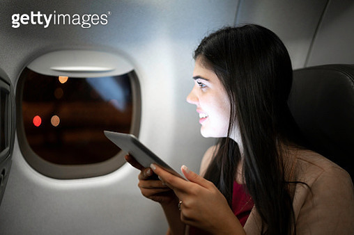 Young woman using tablet on airplane - gettyimageskorea