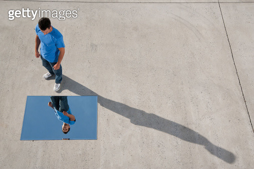 Man standing with mirror on ground and reflection - gettyimageskorea