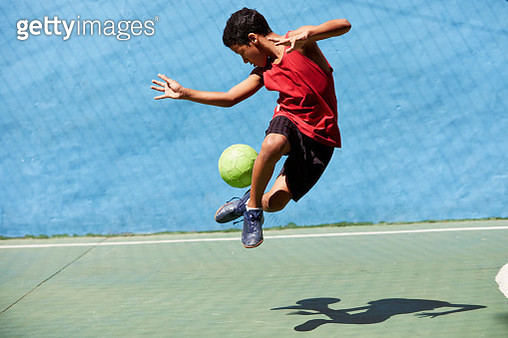 Young Brazilian boy playing football in a brightly coloured football court in a favela in Rio. He is wearing a red vest, black shorts and blue boots. The ball is bright green. - gettyimageskorea