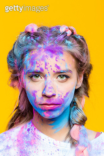 Portrait of serious teenage girl covered in colorful powder after holy festival, looking at camera. Studio shot, yellow background. - gettyimageskorea