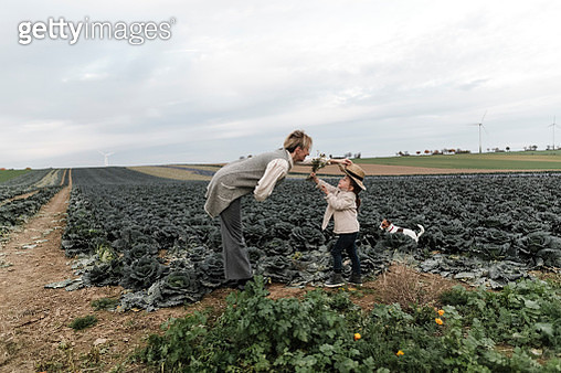 Girl and her mother with dog, straw hat and flowers at a cabbage field - gettyimageskorea