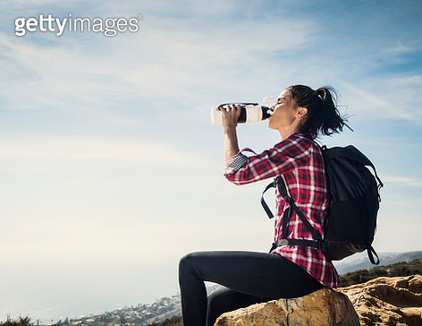 Woman on hike drinking water while sitting on rock - gettyimageskorea