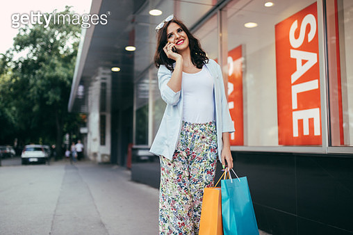 Young woman using phone and carrying shopping bags on a sunny day outdoors - gettyimageskorea
