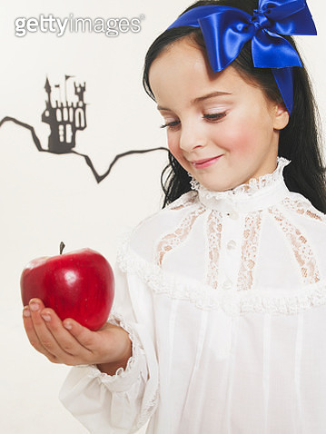 Portrait of little girl dressed up as Snow White looking at red apple - gettyimageskorea