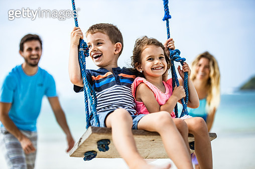 Happy little kids having fun while being pushed by their parents on a swing at the beach. - gettyimageskorea