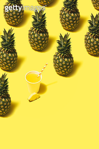 Pineapple juice and pineaaples flat lay on yellow background. - gettyimageskorea