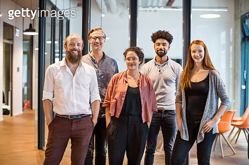 Portrait of confident multi-ethnic business people smiling in creative office - gettyimageskorea