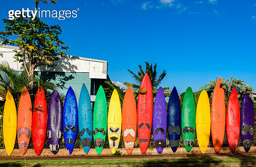 A rainbow colored outdoor fence made out of old, recycled, surfboards in the small town of Paia, Maui, Hawaii. - gettyimageskorea