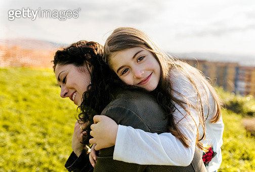 Happy mother carrying daughter outdoors - gettyimageskorea