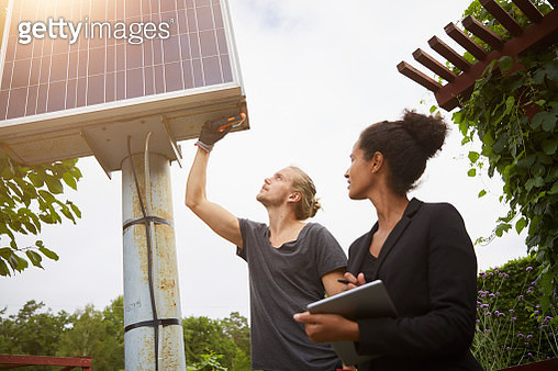 Low angle view of garden architect adjusting solar panel by colleague holding tablet computer - gettyimageskorea
