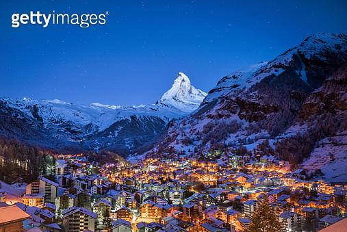 The Matterhorn mountain peak over Zermatt city at night, Switzerland. - gettyimageskorea