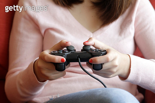 Close-up of teenager hands playing video game - gettyimageskorea