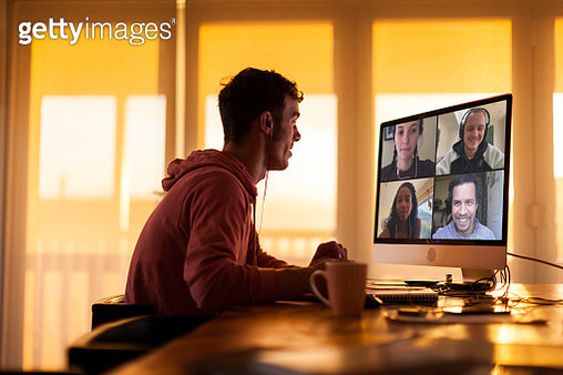 Young man chatting to friends on video call from his home during lockdown - gettyimageskorea