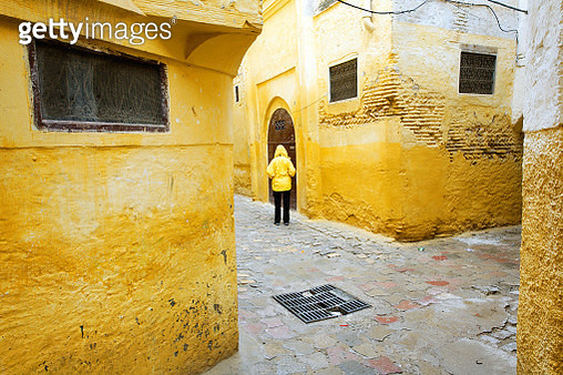 Rear View Of Man Walking At Alley Amidst Houses - gettyimageskorea