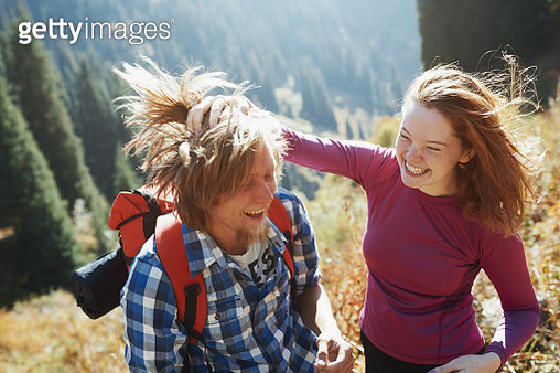 Young adult couple having fun while exploring the mountain nature - gettyimageskorea