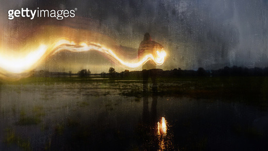 A deliberately blurred, abstract, out of focus, textured edit. Of a ghostly, eerie figure, standing in a flooded field, holding a glowing lamp with a flaming light trail behind. On a winters evening. - gettyimageskorea